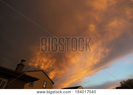 Dark and ominous storm approaching over the rooftops of houses fiery red clouds lit by sunset on front