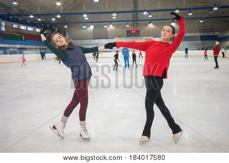 Two graceful girls pose on skate in indoor ice rink, other people out focus