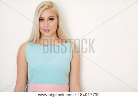 Young pretty blonde in simple dress poses near white wall in studio