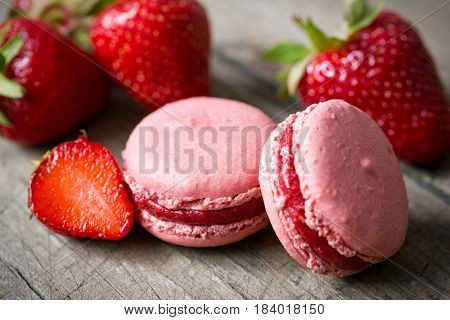 Sweet dessert of red french speciality macaron and a strawberry