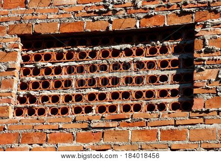 A brick wall with holes. Wall with rounded holes