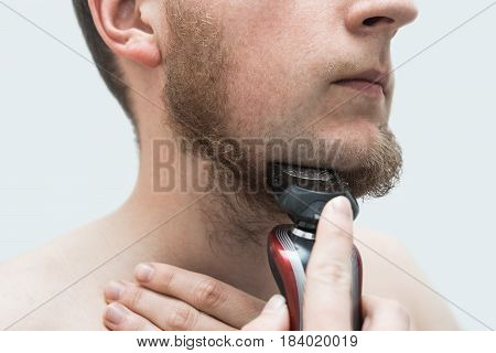 young man shaving his beard off with an electric shaver. Three-quarter view