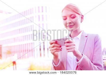 Businesswoman text messaging through smart phone outdoors