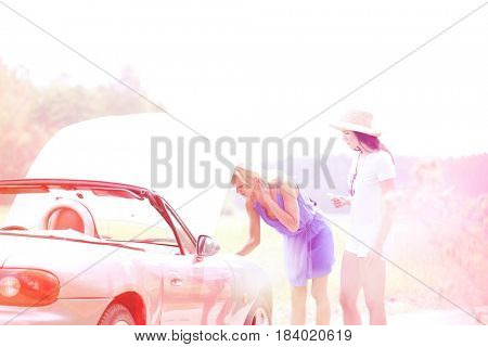 Female friends examining broken down car on country road