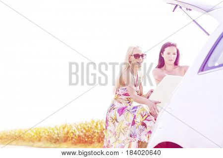 Happy female friends loading luggage in car trunk against clear sky