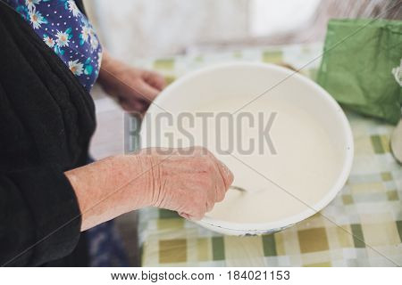 Grandmother mixing batter for pancakes on the kitchen