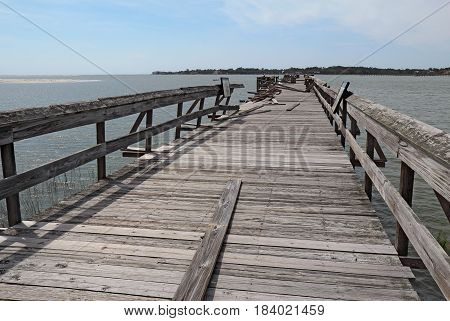 HUNTING ISLAND SOUTH CAROLINA - APRIL 16 2017: Wooden fishing pier at Hunting Island State Park Nature Center shows extensive damage after Hurricane Matthew hit Beaufort County during October of 2016