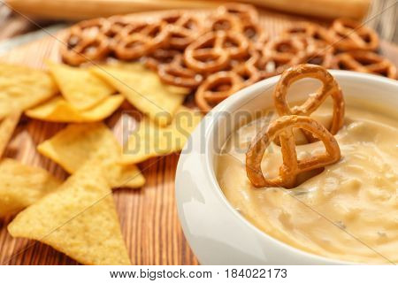 Bowl with beer cheese dip and pretzels on wooden stand