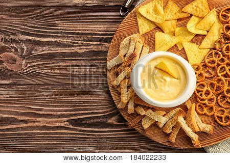 Bowl with beer cheese dip and snacks on wooden board