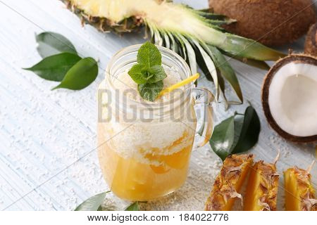 Mason jar with pineapple cocktail on wooden table