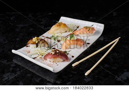 Sushi nigiri set on black marble background. Salmon, eel, prawn and tuna fish served on white plate with chopsticks.