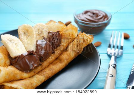 Delicious pancakes with chocolate and banana on blue wooden table