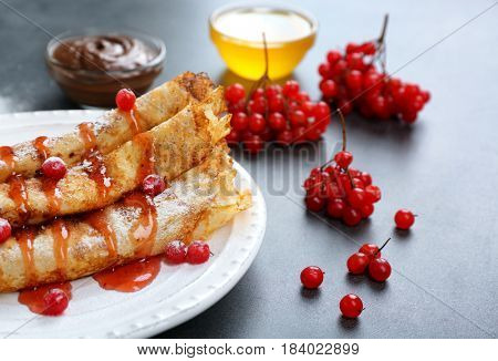 Delicious pancakes with viburnum and sugar powder on white plate
