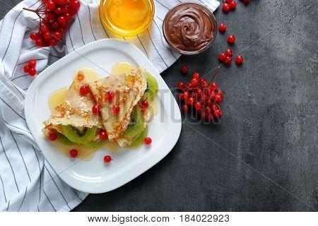 Delicious pancakes with kiwi and viburnum on white plate