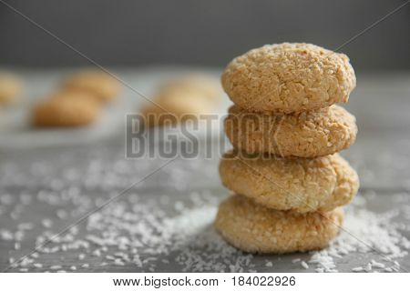 Delicious coconut cookies with flakes on wooden table against blurred background