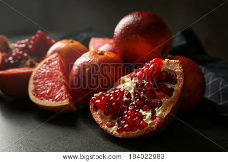 Heap of red citrus fruits and pomegranate on grunge background, closeup