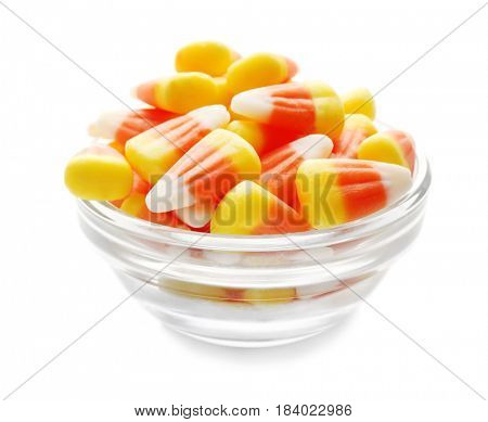 Colorful Halloween candy corns in bowl on white background