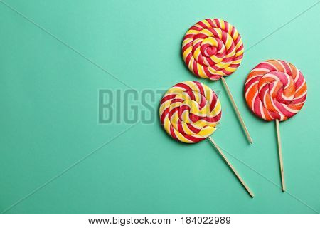 Composition with tasty lollipops on color background