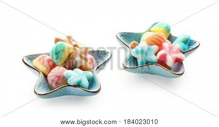 Bowls with tasty jelly candies on white background