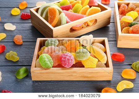 Composition of tasty jelly candies on wooden background