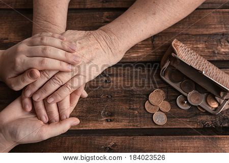 Hands of young and elderly woman and purse with coins on wooden background. Poverty concept