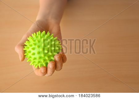 Woman holding rubber ball on wooden background