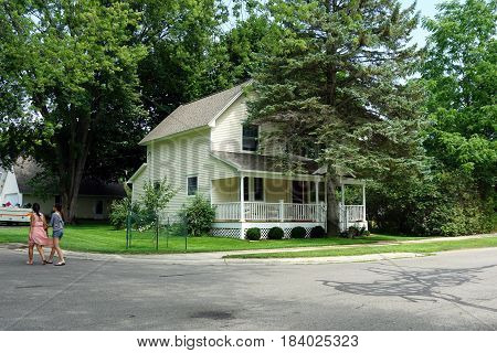 HARBOR SPRINGS, MICHIGAN / UNITED STATES - AUGUST 4, 2016: A single family Victorian home, with a front porch, behind a tall shade tree on Third Street in Harbor Springs.
