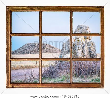 Dusk over prairie with rocks and a butte as seen through vintage, grunge, sash window with dirty glass