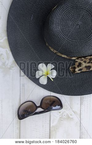 Summer hat with sunglasses on white wooden background.