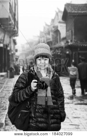 Women tourists holding a camera fun in the ancient city of Feng HuangHunanChinain black and white.