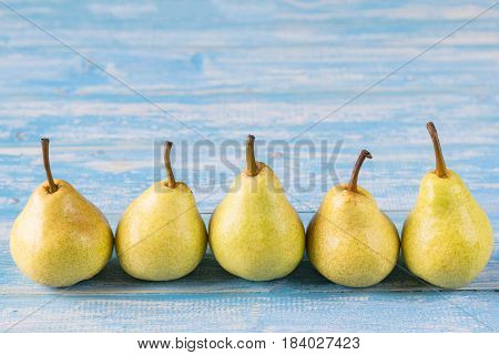 Five Ripe Pears On A Blue Wooden Table.
