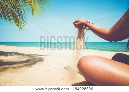 Relaxation and Leisure in Summer lifestyle image of slim tanned girl on beach pours a sand in hand. On hands many seashell bracelets. Tropical island beach