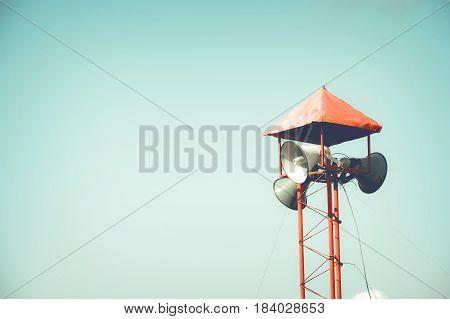 Vintage Horn speaker for public relations sign symbol on blue sky background. vintage color tone effect.