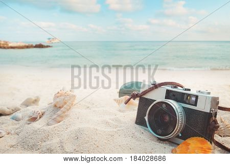 The concept of leisure travel in the summer on a tropical beach seaside. retro camera on the sandbar with starfish shells coral on sandbar and blur sea background. vintage color tone styles.