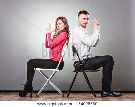 Happy couple having fun and fooling around pretending their hands fingers are guns. Joyful man and woman have nice time sitting back to back. Good relationship.
