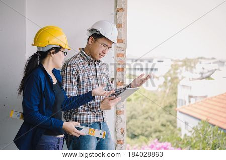 Labor Women And Engineer Discusing With  Tablet On Old Buildings In Their Job Site.