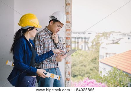 Labor Women And Engineer Serious Discusing With  Tablet On Old Buildings In Their Job Site.