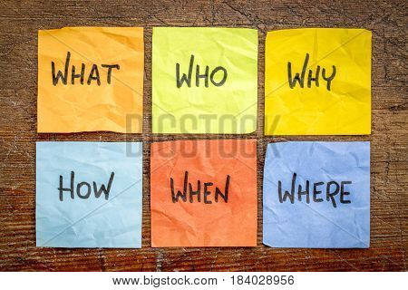 what, who,why,how, when and where questions - uncertainty, brainstorming or decision making concept, colorful crumpled sticky notes on rustic weathered wood