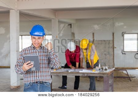Portrait Of Confident Foreman Holding Tablet And Standing At Front Of Labor And Engineer As Discusin