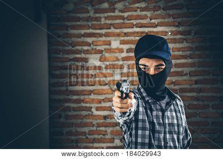 Robber Holding A Gun. Low Key Photo And Selective Focus. Criminality Concept.
