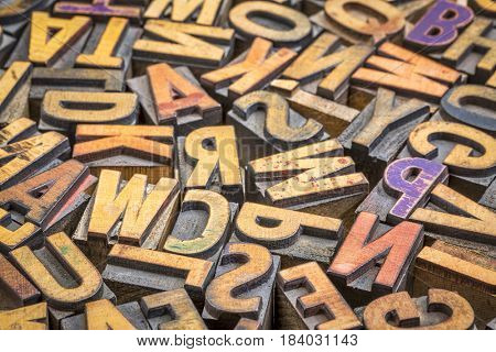 background of random vintage letterpress printing blocks on a grunge rustic wood