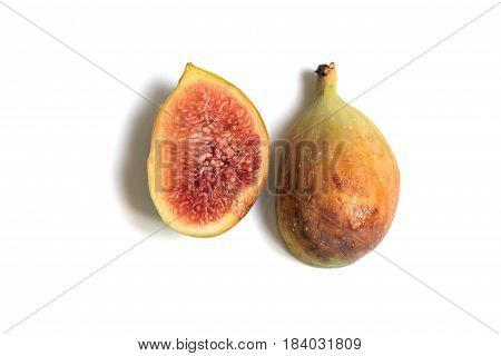 Ripe common fig cut through to show the red flesh and seeds on white background.