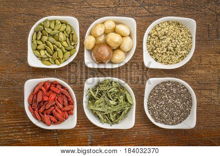 collection of superfoods in small ceramic bowls against rustic wood: pumpkin seeds, macadamia nuts, hemp seed hearts, goji berry, stevia herb and chia seeds
