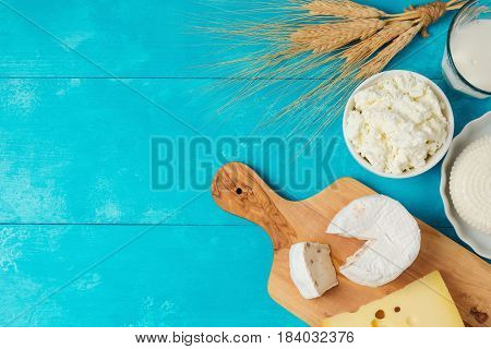 Milk and cheese dairy products on wooden blue background. Jewish holiday Shavuot concept. View from above