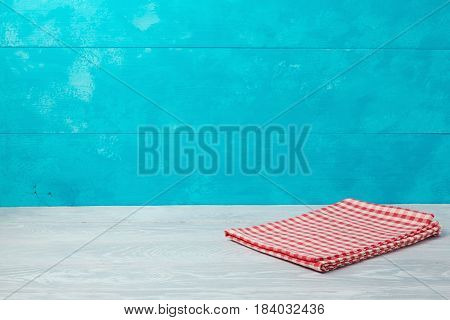 Empty wooden deck table with checked red tablecloth over rustic blue background. Summer nautical concept