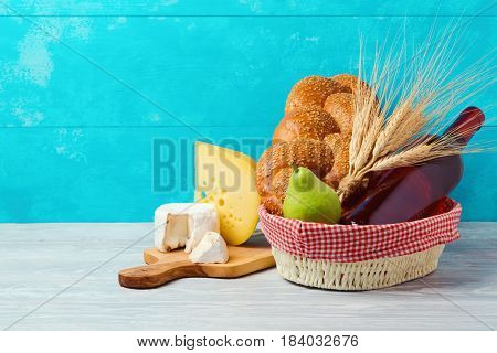 Basket with wine bottle bread and cheese on wooden table. Jewish holiday Shavuot concept.