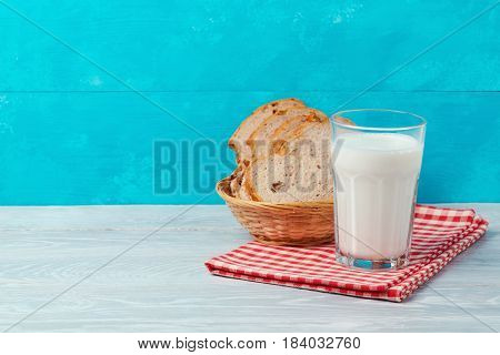 Milk and bread on wooden table over blue background with copy space. Jewish holiday Shavuot concept