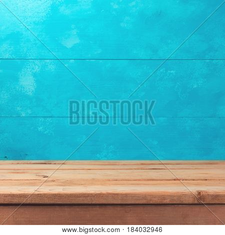 Empty wooden deck table over rustic blue background. Summer nautical concept