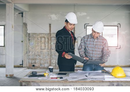 Management consulting with engineers working with blueprint and drawing on work table in for management business plan and construction site project.