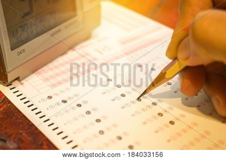 alarm digital clock on optical form standardized test with bubbled and a black pencil examination for answer sheet education concept